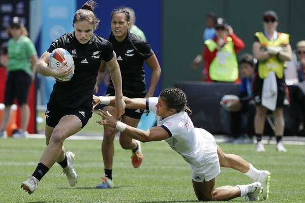 New Zealand's Michaela Blyde, left, runs past United States's Nicole Heavirland, right, to score during a Women's Rugby Sevens World Cup semifinal in San Francisco, Saturday, July 21, 2018. (AP Photo/Jeff Chiu)