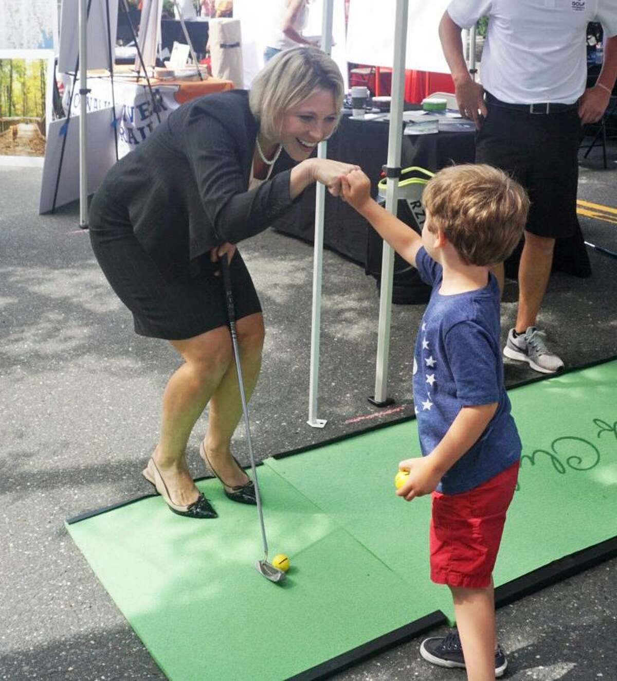 Sue Hatfield, Republican endorsed candidate for attorney general, pounded fists with Jaime Shantz, 5, of Ridgefield at the Ridgefield Sidewalk Sales on Saturday July 21, 2018.