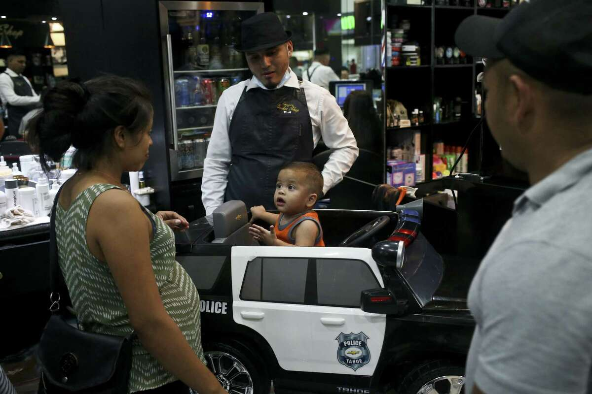 Watched by his parents, year-old son Johan Bueso Montecinos, who became a poster child for the U.S. policy of separating immigrants and their children, gets a hair cut, in San Pedro Sula, Honduras, Friday, 20, 2018. Johan Bueso Montecinos arrived in San Pedro Sula and was reunited with his parents on a government bus. Captured by Border Patrol agents in March, Johan?'s father was deported and the then 10-month-old remained at an Arizona shelter. (AP Photo/Esteban Felix)