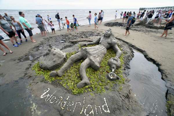 People walk by the entry titled, Wonderland, depicting Alice in Wonderland created by the Burgess and Hopkins families of Shelton at the Milford Arts Council's 41st Annual Sand Sculpture Competition at Walnut Beach in Milford on July 21, 2018.