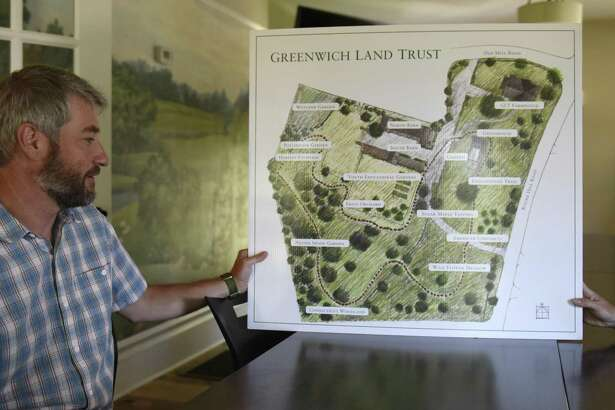 Greenwich Land Trust Executive Director Will Kies shows a map of the new accessible walking trail at the Greenwich Land Trust Mueller Preserve in Greenwich, Conn. Thursday, July 19, 2018. The new trail traverses four acres of land showing a variety of different habitats and ecosystems, a microcosm of those found throughout the town, over the short loop.