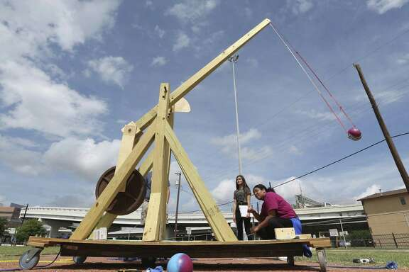 Advanced Learning Academy pre-calculus student Sarah Gonzalez kneels as she pulls the pin to launch a 2-pound ball across the Fox Tech High School football field using a wooden trebuchet the pre-calculus students designed and built in this May 22 photo. San Antonio Independent School District's decision to build its new central office on the football field highlights the dilemma facing SAISD as it tries to staunch hemorrhaging enrollment in part by courting middle-class families who expect schools with academics and amenities found in wealthier school districts.