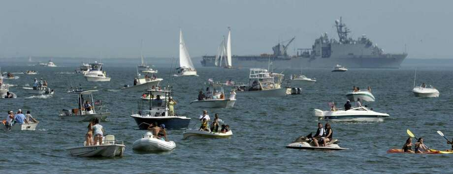A flotilla of small craft fill Niantic Bay off East Lyme, Conn., as the USS Carter Hall is moored offshore Friday, July 6, 2012 to kick off festivities in OpSail 2012.  The USS Carter Hall will join a Parade of Sail into New London Harbor Saturday morning as part of the OpSail event commemorating the 200th Anniversary to the War of 1812 and the penning of the U.S. National Anthem, The Star Spangled Banner during that war. (AP Photo/The Day, Sean D. Elliot)  MANDATORY CREDIT Photo: SEAN D. ELLIOT / Associated Press / 2012 The Day Publishing Company
