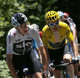 Britain's Chris Froome, left, and Britain's Geraint Thomas, wearing the overall leader's yellow jersey, climb during the twelfth stage of the Tour de France cycling race over 175.5 kilometers (109 miles) with start in Bourg-Saint-Maurice Les Arcs and Alpe d'Huez, France, Thursday July 19, 2018. (AP Photo/Peter Dejong)