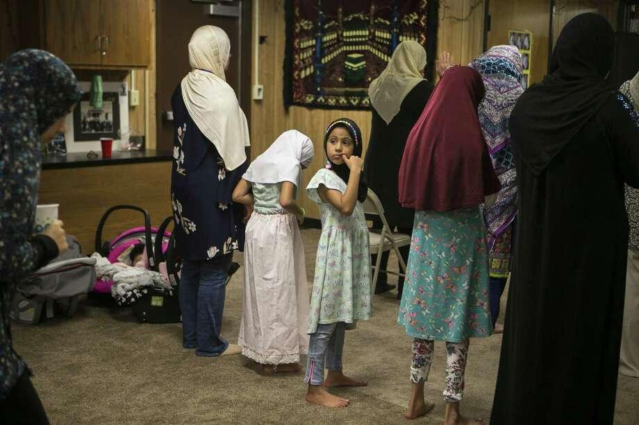 Janah Abd, 6, turns around during evening prayer at the Victoria Islamic Center. Photo: Josie Norris / Staff Photographer / © San Antonio Express-News