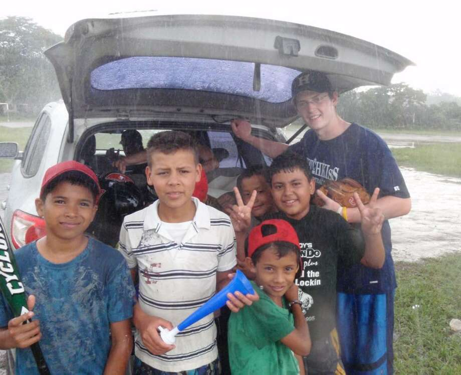 Preston Burke and children seek shelter under a hatchback during a typical afternoon down pour in Honduras in July. Photo: Contributed Photo / Greenwich Time Contributed