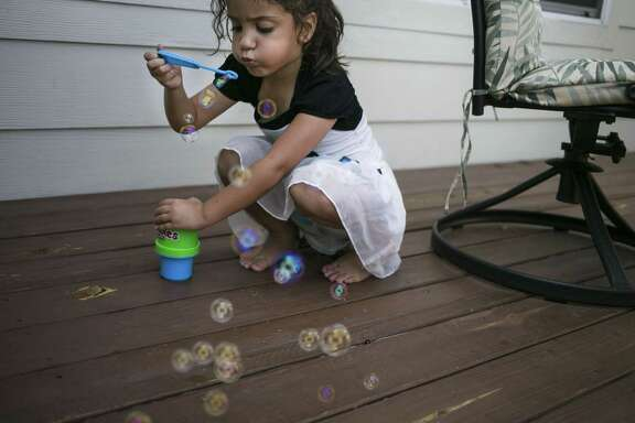 Huda Nusayr, 4, blows bubbles at her family's home in Victoria July 20, 2018.