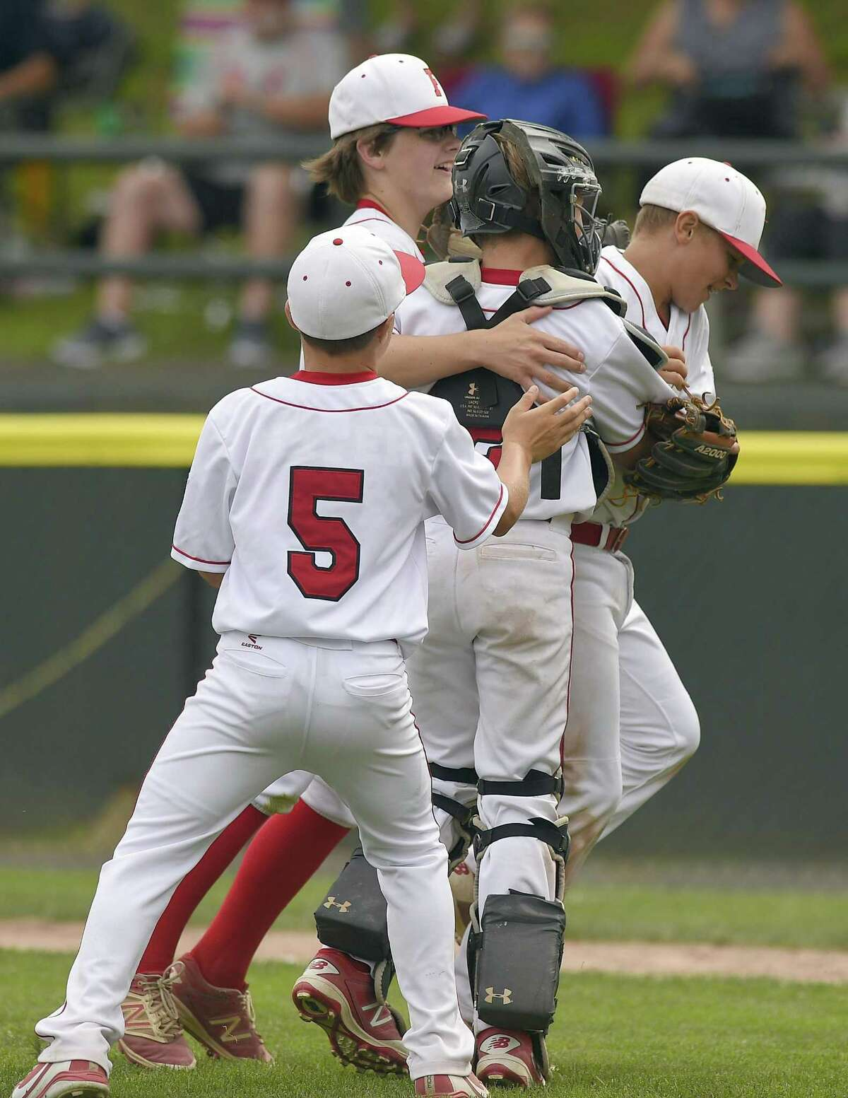 Fairfield American players Jude Gussen (5), Pierce Cowles (8), catcher Timmy Domizio (2) and relief pitcher Charlie Yates (18) celebrate their 5-2 win over Milford in a Section 1 Little League Championship at Drotar Park on July 21, 2018 in Stamford, Connecticut.