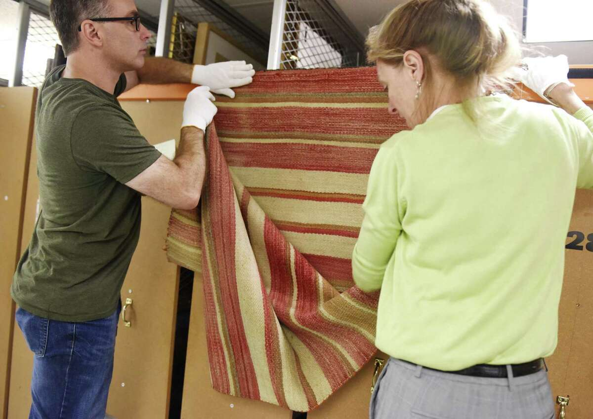 Collections Manager Timothy Walsh, left, and Registrar and Exhibit Curator Kirsten Reinhardt show a colorful 1880s serape from the collections storage area in the Bruce Museum in Greenwich, Conn. Tuesday, July 17, 2018. The new exhibit,
