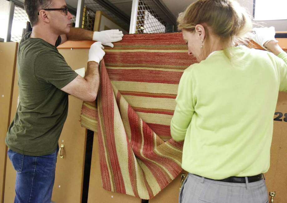 "Collections Manager Timothy Walsh, left, and Registrar and Exhibit Curator Kirsten Reinhardt show a colorful 1880s serape from the collections storage area in the Bruce Museum in Greenwich, Conn. Tuesday, July 17, 2018. The new exhibit, ""A Continuous Thread: Navajo Weaving Traditions,"" will trace the history of the Navajo weaving tradition from the earliest Mexican-inspired Saltillo serapes, c. 1880, to mid-20th century pictorial rugs. The show opens August 18 and will run through late November. Photo: Tyler Sizemore / Hearst Connecticut Media / Greenwich Time"