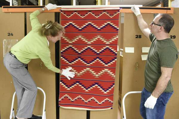 "Registrar and Exhibit Curator Kirsten Reinhardt, left, and Collections Manager Timothy Walsh show a traditional eyedazzler pattern rug, dated between 1965 and 1985, from the collections storage area in the Bruce Museum in Greenwich, Conn. Tuesday, July 17, 2018. The new exhibit, ""A Continuous Thread: Navajo Weaving Traditions,"" will trace the history of the Navajo weaving tradition from the earliest Mexican-inspired Saltillo serapes, c. 1880, to mid-20th century pictorial rugs. The show opens August 18 and will run through late November."