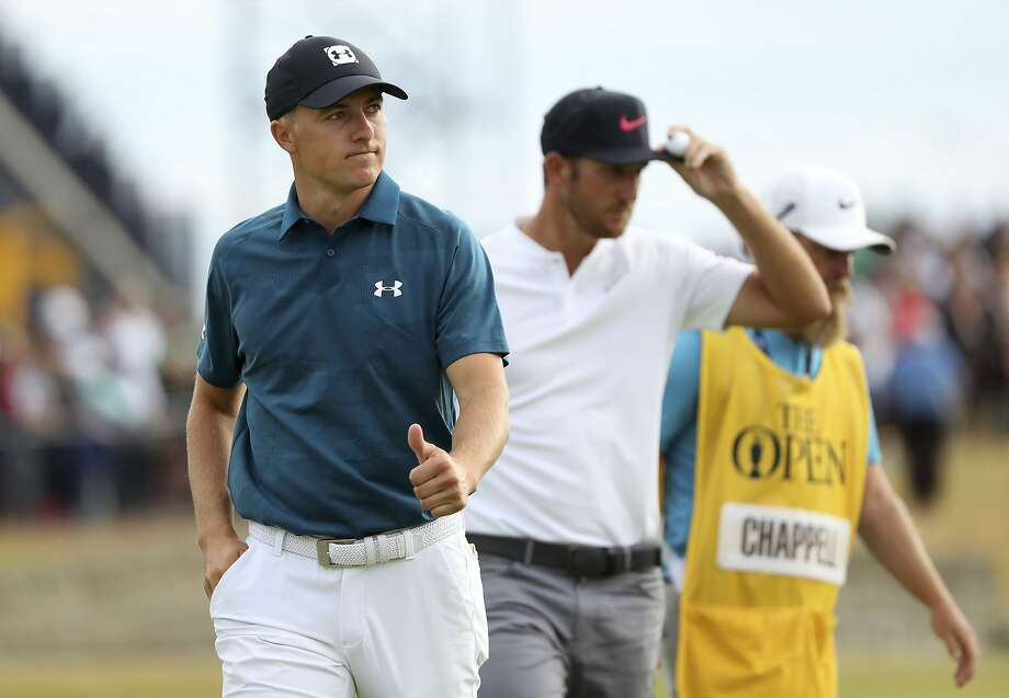 Jordan Spieth (left) gives his round a thumbs up after he and Kevin Chappell finish their third round, while Tiger Woods (right) shot his best round at a major since 2010 to rise into contention. Photo: Peter Morrison / Associated Press