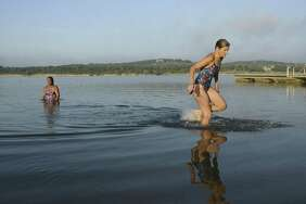 Susan O'Brien, right, and Rosana Andrade, who are members of the Masters of South Texas group, get of out of the water after swimming across Boerne City Lake on Saturday morning, July 21, 2018. They participate in swimming competitions and open water swims. Many users of the lake are concerned about a plan by KB Homes to build a residential subdivision next to the lake.
