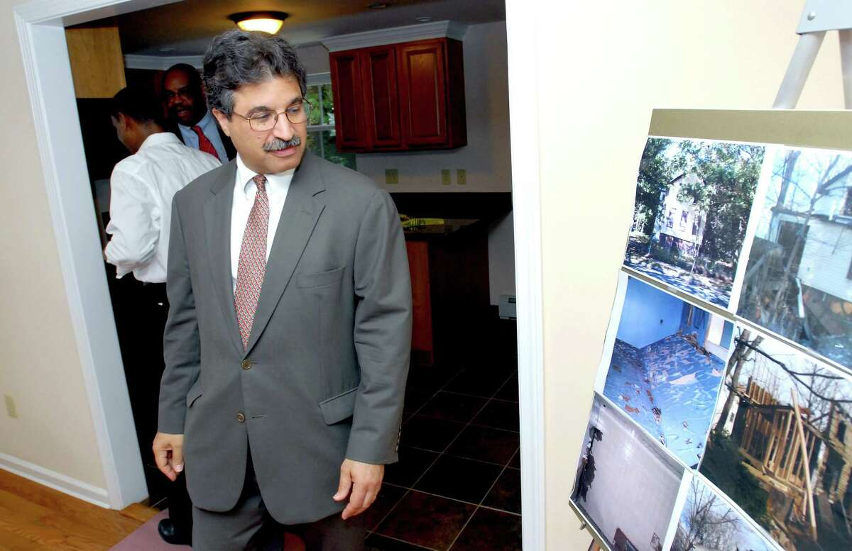 In this file photo, William Ginsberg, president and CEO of The Community Foundation for Greater New Haven, glances at old photographs of 692 Orchard St. in New Haven during a celebration of the completion of the home by the Beulah Land Development Corp. in 2010.