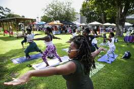 Areka Bannister, center, holds a pose in Yoga with Letty on Saturday at the Free Market Square, part of Project Row House's strategic art plan to highlight entrepreneurship and artistic performance in the Third Ward.