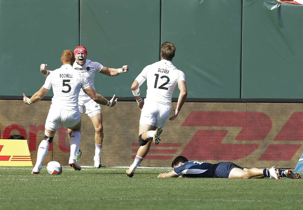 England's Phil Burgess, left, celebrates with James Rodwell (5) and Harry Glover (12) after scoring past United States's Madison Hughes, bottom, during the Rugby Sevens World Cup in San Francisco, Saturday, July 21, 2018. (AP Photo/Jeff Chiu)