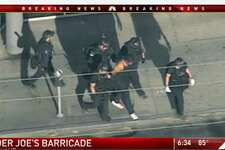 In this image from video provided by KNBC-TV, police officers escort a suspect away from a Trader Joe's supermarket in the Silver Lake district of Los Angeles Saturday, July 21, 2018. (KNBC-TV via AP)
