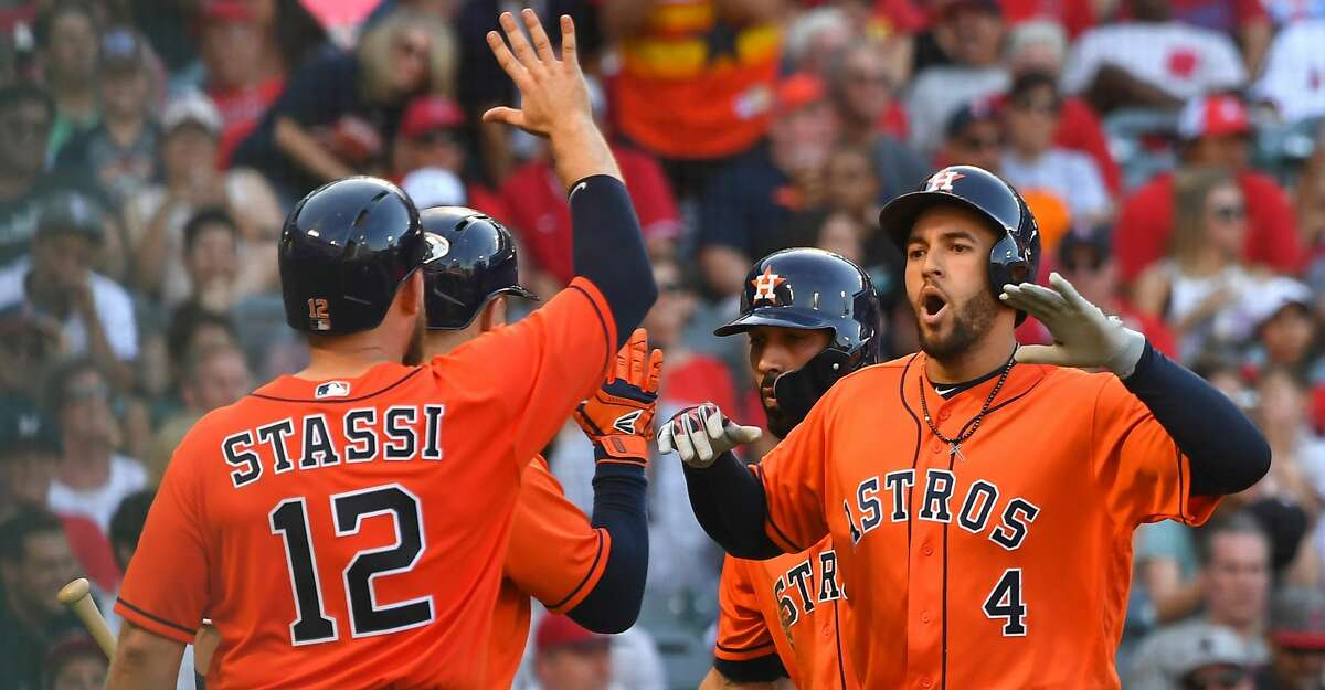 ANAHEIM, CA - JULY 21: George Springer #4 celebrates with Max Stassi #12 of the Houston Astros as he crosses the plate after hitting a grand slam home run in the sixth inning of the game off relief pitcher Taylor Cole #67 of the Los Angeles Angels of Anaheim at Angel Stadium on July 21, 2018 in Anaheim, California. (Photo by Jayne Kamin-Oncea/Getty Images)