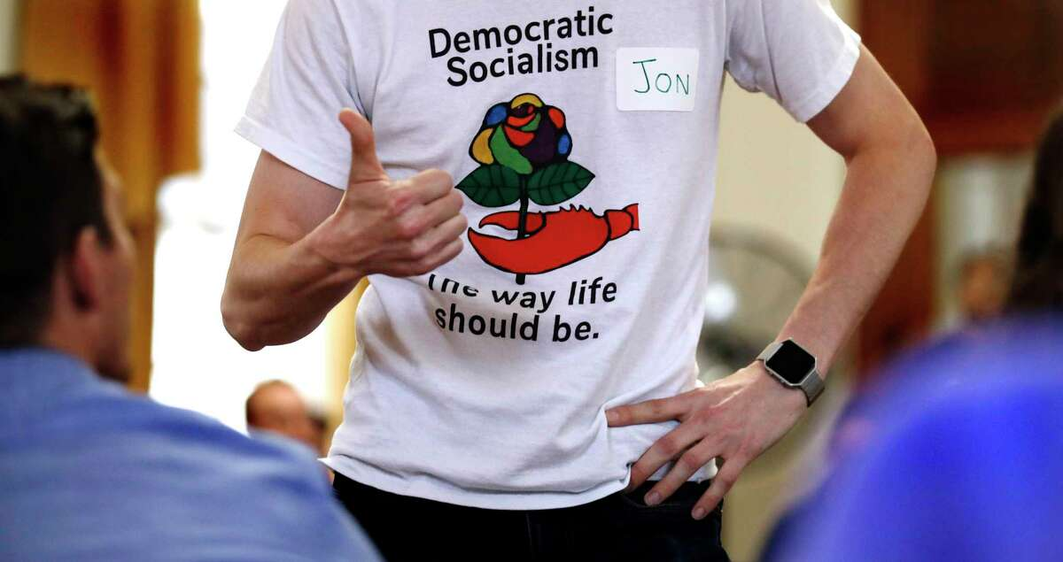 Jon Torsch, center, wears a t-shirt promoting democratic socialism during a gathering of the Southern Maine Democratic Socialists of America at City Hall in Portland, Maine, Monday, July 16, 2018. On the ground in dozens of states, there is new evidence that democratic socialism is taking hold as a significant force in Democratic politics. (AP Photo/Charles Krupa)