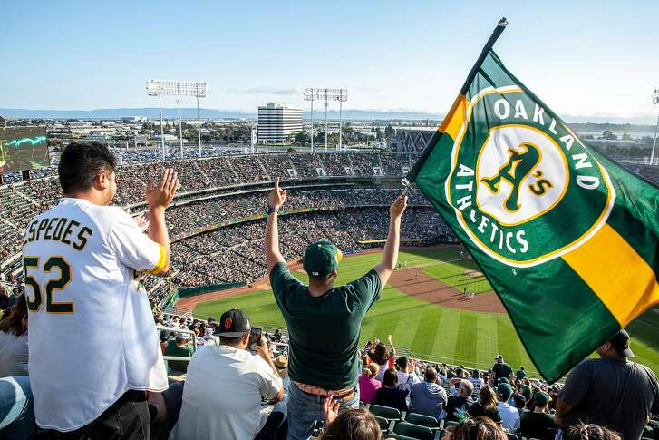 From left: Andres Espinoza stands and cheers as Juan Contreras of Stockton waves an Oakland A's flag at the top of Oakland Coliseum's Mount Davis during an MLB game between the A's and the San Francisco Giants on Saturday, July 21, 2018, in Oakland, Calif. For the first time in 13 years, the A�s opened Mount Davis, the tallest deck in the Oakland Coliseum.