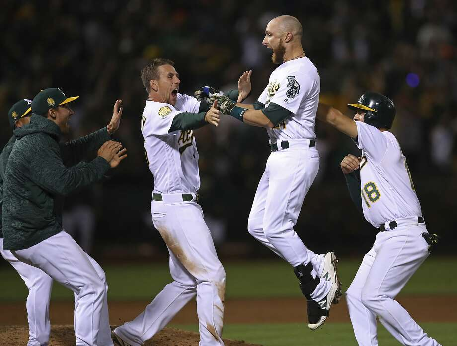 Oakland Athletics' Jonathan Lucroy, second from right, celebrates with Chad Pinder (18) and Stephen Piscotty, second from left, after driving in the winning run against the San Francisco Giants in the 11th inning of a baseball game Saturday, July 21, 2018, in Oakland, Calif.  Photo: Ben Margot, Associated Press