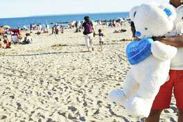 A beachgoer holds a teddy bear prize from the amusement park at Coney Island in the Brooklyn Borough of New York on July 7, 2018.