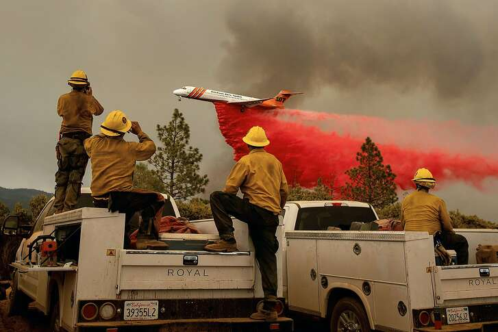 TOPSHOT - Firefighters watch as an air tanker drops retardant while battling the Ferguson fire in the Stanislaus National Forest, near Yosemite National Park, California on July 21, 2018. A fire that claimed the life of one firefighter and injured two others near California's Yosemite national park has almost doubled in size in three days, authorities said Friday. The US Department of Agriculture (USDA) said the so-called Ferguson fire had spread to an area of 22,892 acres (92.6 square kilometers), and is so far only 7 percent contained.   / AFP PHOTO / NOAH BERGERNOAH BERGER/AFP/Getty Images