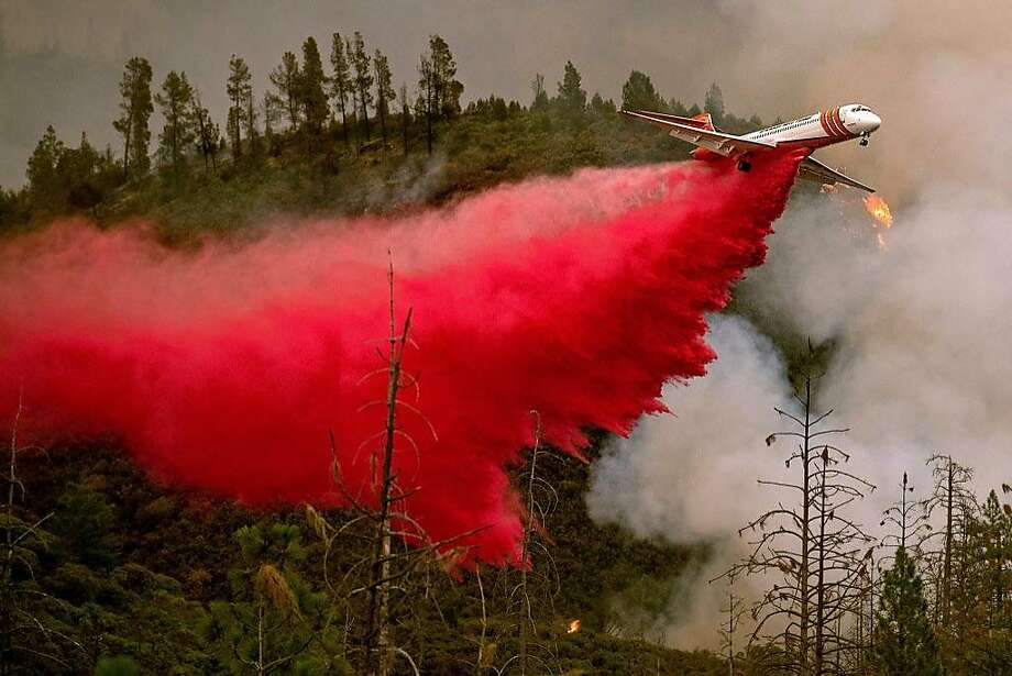 An air tanker drops retardant while battling the Ferguson fire in Stanislaus National Forest, near Yosemite National Park, California on July 21, 2018. A fire that claimed the life of one firefighter and injured two others near California's Yosemite national park has almost doubled in size in three days, authorities said Friday. The US Department of Agriculture (USDA) said the so-called Ferguson fire had spread to an area of 22,892 acres (92.6 square kilometers), and is so far only 7 percent contained.   / AFP PHOTO / NOAH BERGERNOAH BERGER/AFP/Getty Images Photo: NOAH BERGER, AFP/Getty Images