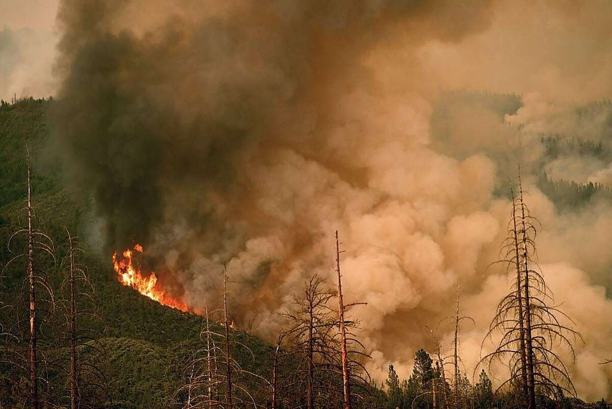 Flames from the Ferguson fire crest a hill in Stanislaus National Forest, near Yosemite National Park, California on July 21, 2018.