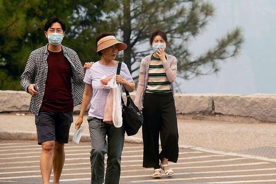 Tourists wear masks while visiting Yosemite National Park, California, as smoke from the Ferguson fire fills the air on July 21, 2018. A fire that claimed the life of one firefighter and injured two others near California's Yosemite national park has almost doubled in size in three days, authorities said Friday. The US Department of Agriculture (USDA) said the so-called Ferguson fire had spread to an area of 22,892 acres (92.6 square kilometers), and is so far only 7 percent contained. Photo: Noah Berger / AFP / Getty Images