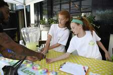 Sam Buck's classmates Devon O'Loughnane, 12, and Addison O'Loughnane sell lemonade to raise money to help Sam, who has Vanishing White Matter Disease, at the 2018 Sidewalk Sale Days in downtown Greenwich, Conn. Thursday, July 12, 2018.
