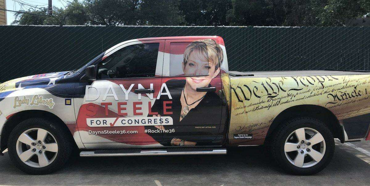 """Dayna Steele, the 2018 Democratic candidate for Texas' 36th Congressional District, drives a 2012 Dodge Ram decorated with pictures of the Declaration of Independence, an American flag and a self-portrait with the caption """"photo not actual size."""""""