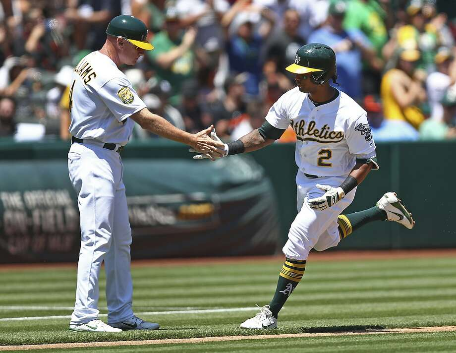 Oakland Athletics' Khris Davis, right, is congratulated by third base coach Matt Williams after hitting a two-run home run off San Francisco Giants' Johnny Cueto in the first inning of a baseball game Sunday, July 22, 2018, in Oakland, Calif. (AP Photo/Ben Margot) Photo: Ben Margot / Associated Press