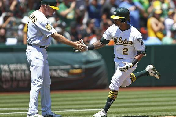 Oakland Athletics' Khris Davis, right, is congratulated by third base coach Matt Williams after hitting a two-run home run off San Francisco Giants' Johnny Cueto in the first inning of a baseball game Sunday, July 22, 2018, in Oakland, Calif. (AP Photo/Ben Margot)