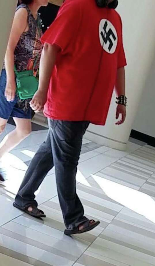 A photo taken by a patron at Crossgates Mall Friday, July 20, 2018 shows an unidentified man wearing a shirt that looks like the Nazi flag. (Provided)