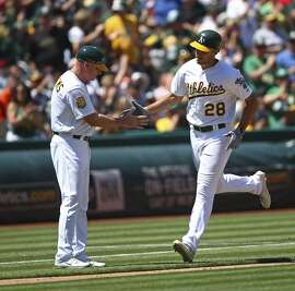 Oakland Athletics' Matt Olson, right, is congratulated by third base coach Matt Williams after hitting a home run off San Francisco Giants' Johnny Cueto in the sixth inning of a baseball game Sunday, July 22, 2018, in Oakland, Calif. (AP Photo/Ben Margot)