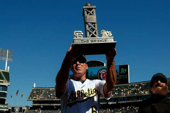 OAKLAND, CA - JULY 22:  Bob Melvin #6 of the Oakland Athletics holds up The Bridge trophy awarded for winning the series against the San Francisco Giants after the game at the Oakland Coliseum on July 22, 2018 in Oakland, California. The Oakland Athletics defeated the San Francisco Giants 6-5 in 10 innings. (Photo by Jason O. Watson/Getty Images)