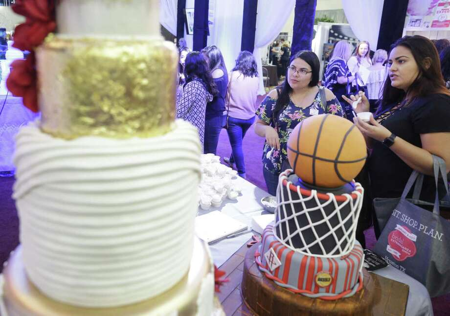 Yrene Molina, maid of honor, left, and  Berenile Duque, bride, right, both of Houston sample cake at the Edible Designs booth during the Bridal Extravaganza held at the George R. Brown Convention Center Sunday, July 22, 2018, in Houston.  ( Melissa Phillip / Houston Chronicle ) Photo: Melissa Phillip, Staff / Houston Chronicle / © 2018 Houston Chronicle