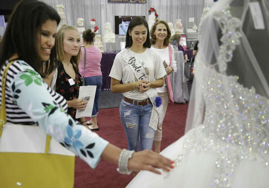 "Houston Bridal Flea will have ""pre-loved"" items for sale during its event Sept. 9 at 2203 Preston St. Pictured is Sonia Landeche, of Weimar, left, mother of the bride, Savannah Jacobs, of Schulenburg, a bridesmaid, Kaylee Landeche, of Weimar, bride, and her grandmother Lala Garza, of New Braunfels, right, looking a bridal gown during the Bridal Extravaganza held at the George R. Brown Convention Center Sunday, July 22, 2018, in Houston. ( Melissa Phillip / Houston Chronicle )  Photo: Melissa Phillip, Staff / Houston Chronicle / © 2018 Houston Chronicle"
