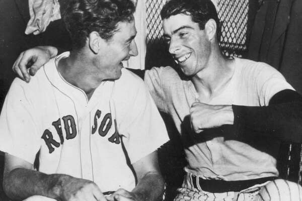 """FILE - In this July 8, 1941, file photo, Joe DiMaggio, right, of the New York Yankees, congratulates Boston Red Sox slugger Ted Williams whose ninth inning homer defeated the national league All Stars, 7-5, in Detroit, Mich. A new film explores the life of baseball legend Williams who struggled with his Mexican-American heritage and his volatile relationship with his family and the press. The upcoming PBS """"American Masters"""" documentary on the former Boston Red Sox slugger uses rare footage and family interviews to paint a picture of a complicated figure that hid his past but later spoke out and defended black players. (AP Photo/File)"""