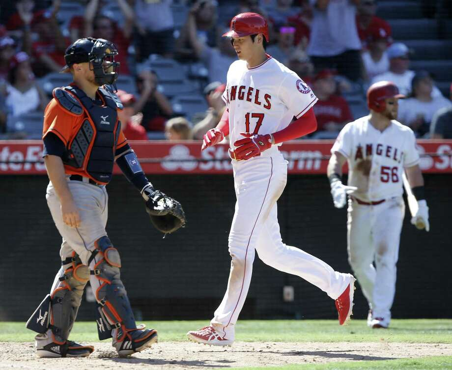 Los Angeles Angels designated hitter Shohei Ohtani (17), of Japan, scores without a throw to Houston Astros catcher Tim Federowicz, left, on a two-run single by David Fletcher during the seventh inning of a baseball game in Anaheim, Calif., Sunday. Photo: Alex Gallardo, FRE / Associated Press / FR170211 AP