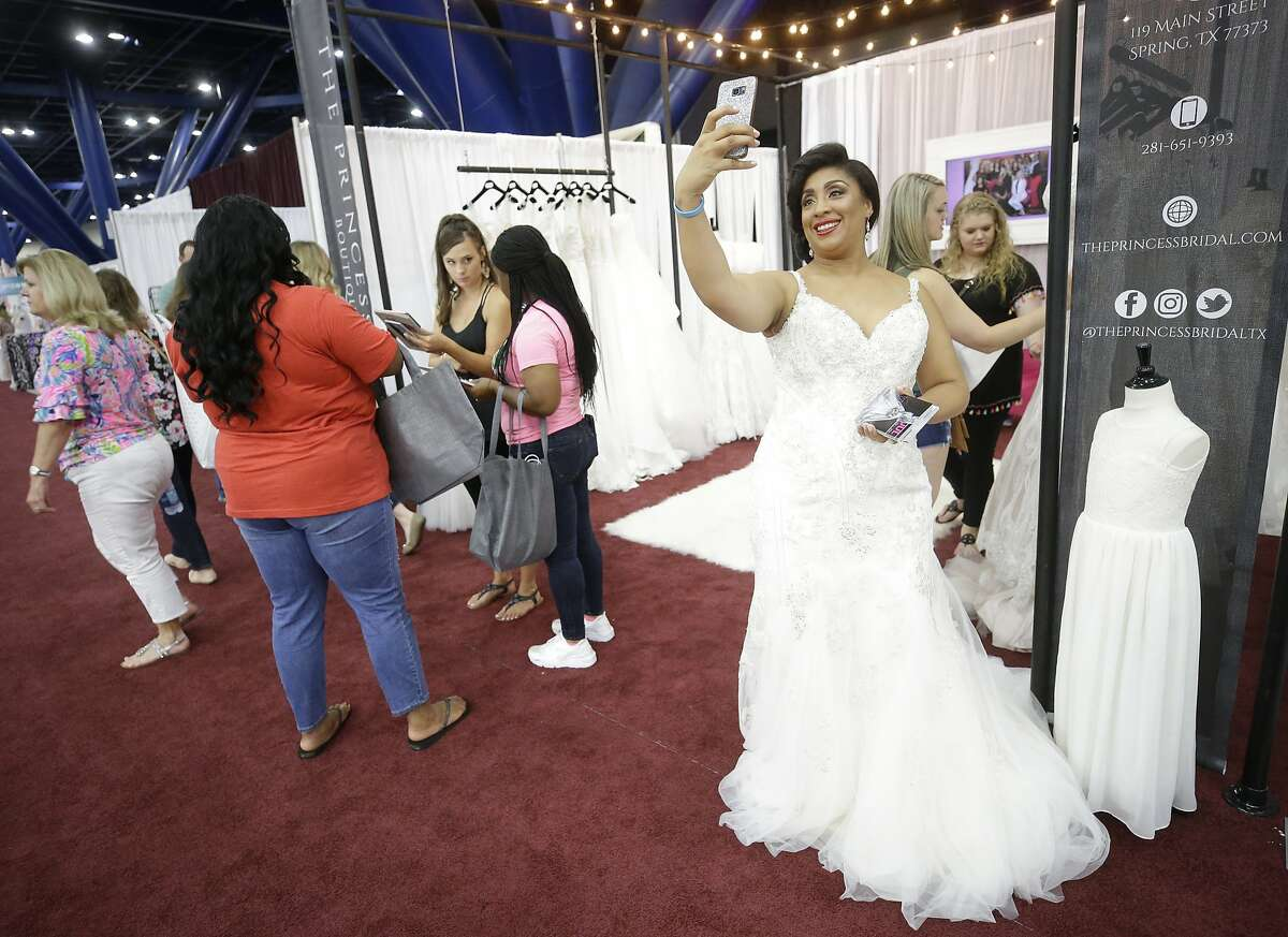Rashieda Bluiett takes a selfie as she models a wedding gown at The Princess Bridal booth during the Bridal Extravaganza held at the George R. Brown Convention Center Sunday, July 22, 2018, in Houston.