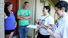Celina Montoya (center) talks with Doug Sims and Beth Sims at the front door of their home on the north side as Democrats in red districts in San Antonio mount their campaigns to take state office on July 14, 2018.  Working with Montoya is campaign volunteer Alisha King (right).