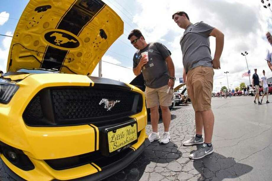"Dan and Zach McCaslin of Vandalia examine ""Little Miss Sunshine,"" one of the Mustangs at the 41st Annual Mustang Round-up on Saturday in Alton. Photo:       David Blanchette 