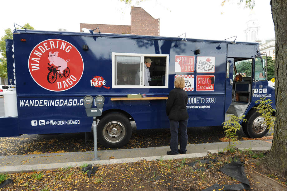 Andrea Loguidice talks to a customer as her boyfriend Brandon Snooks cooks the order on the Wandering Dago food truck outside Schenectady County Public Library Tuesday, Oct. 9, 2012 in Schenectady, N.Y. (Lori Van Buren / Times Union) ORG XMIT: MER2013082719341471 Photo: Lori Van Buren / 00019582A