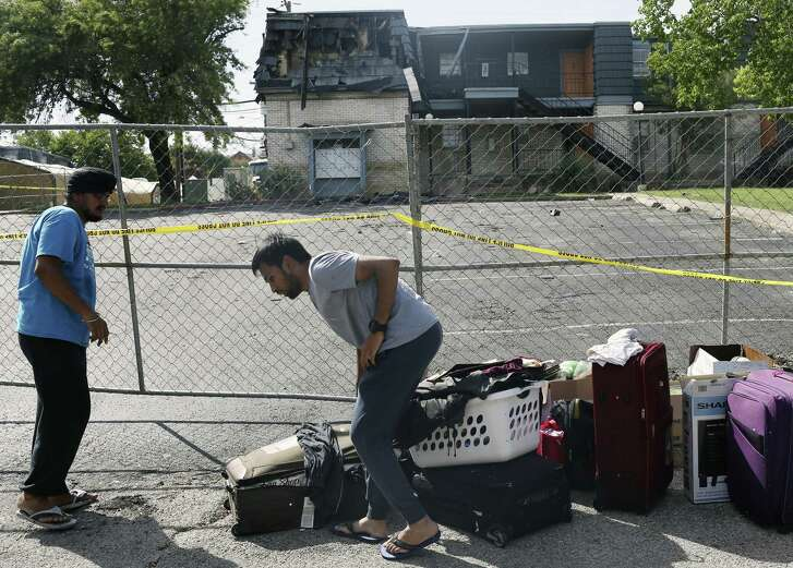 Shashank Pallerla, right, helps out his friend, Goldi Makhija remove belongings from his apartment after a fire at the Iconic Village Apartments in San Marcos, Texas, Sunday, July 22, 2018. Emergency personnel have recovered three bodies and two remain unaccounted. The fire started at 4:30 a.m. and affected about 200 residents.
