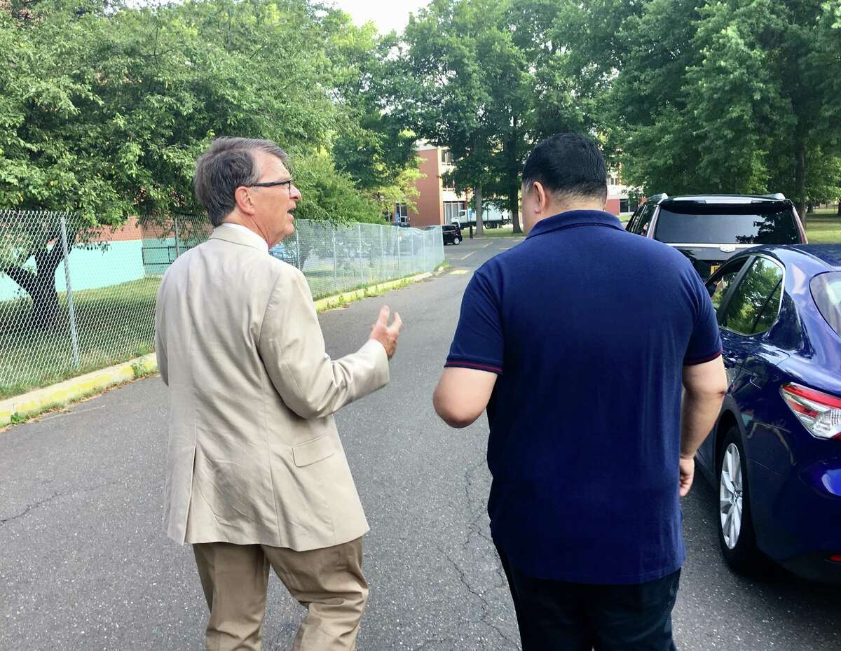 University of Connecticut general counsel Rich Orr, left, walks with Bruno Wu, chairman and CEO of Seven Stars Cloud Inc., at the former UConn West Hartford campus that Wu is buying and hopes to convert into a technology hub.