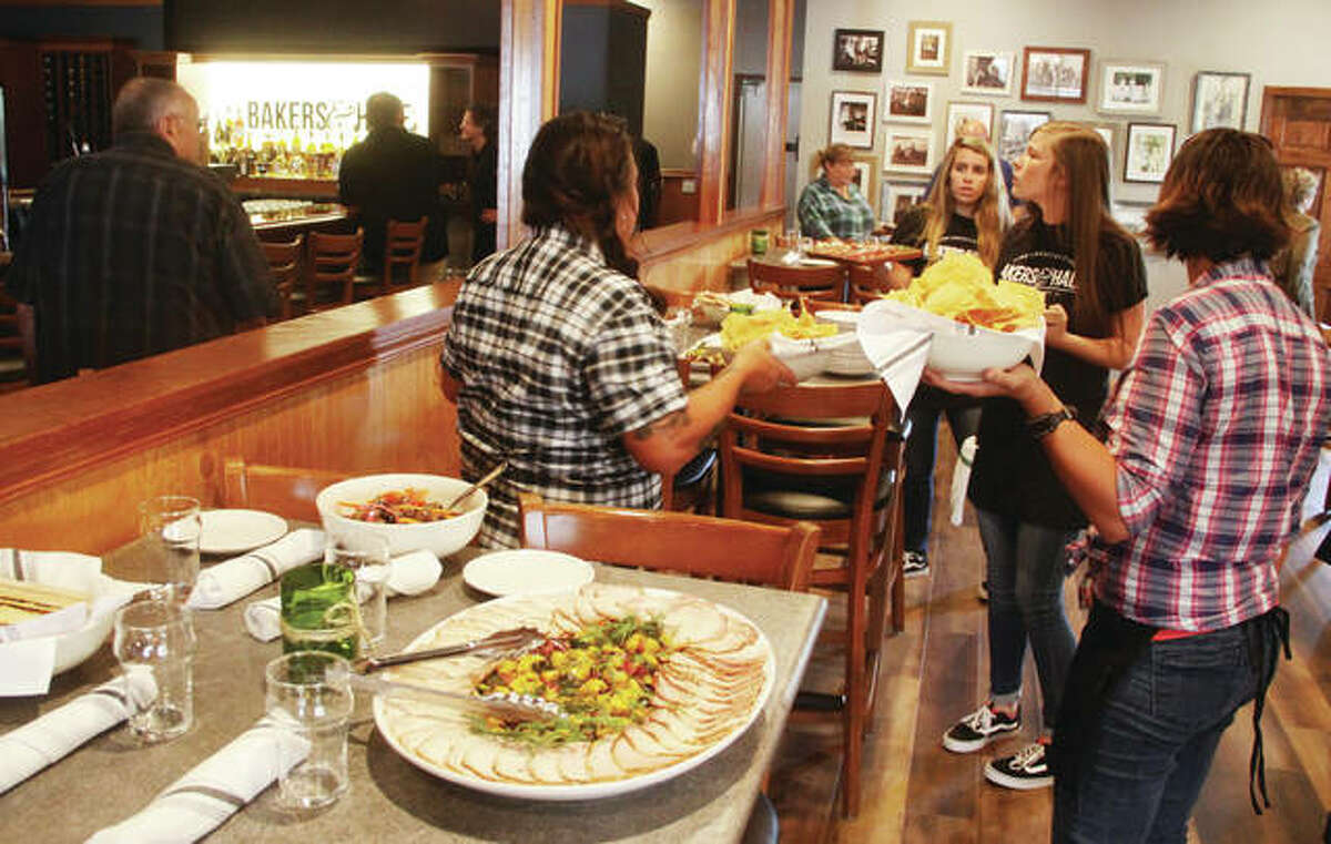 Servers put out food for guests at a ribbon-cutting ceremony Thursday at the new Godfrey Restaurant Bakers & Hale, located at 7120 Montclair Ave.