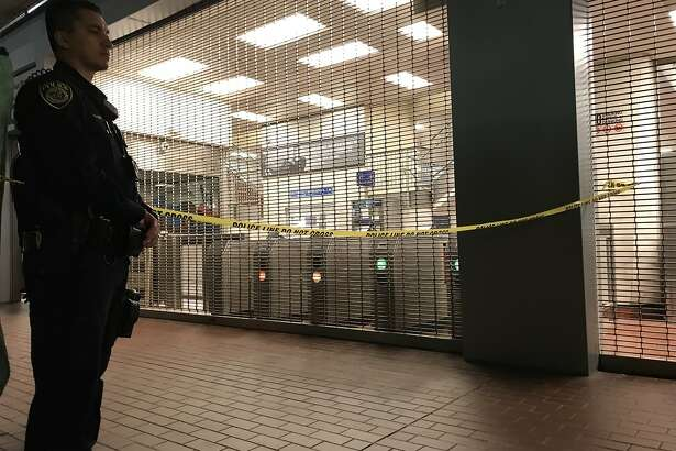 A police officer stands outside the closed MacArthur BART Station in Oakland after a homicide on Sunday, July 22, 2018.