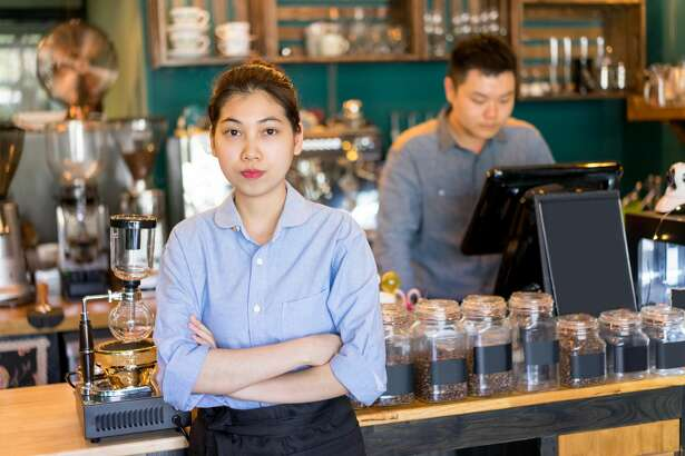 Serious confident young Asian owner working in coffee house. Strict coffee house manager crossing arms on chest and looking at camera. Entrepreneur concept